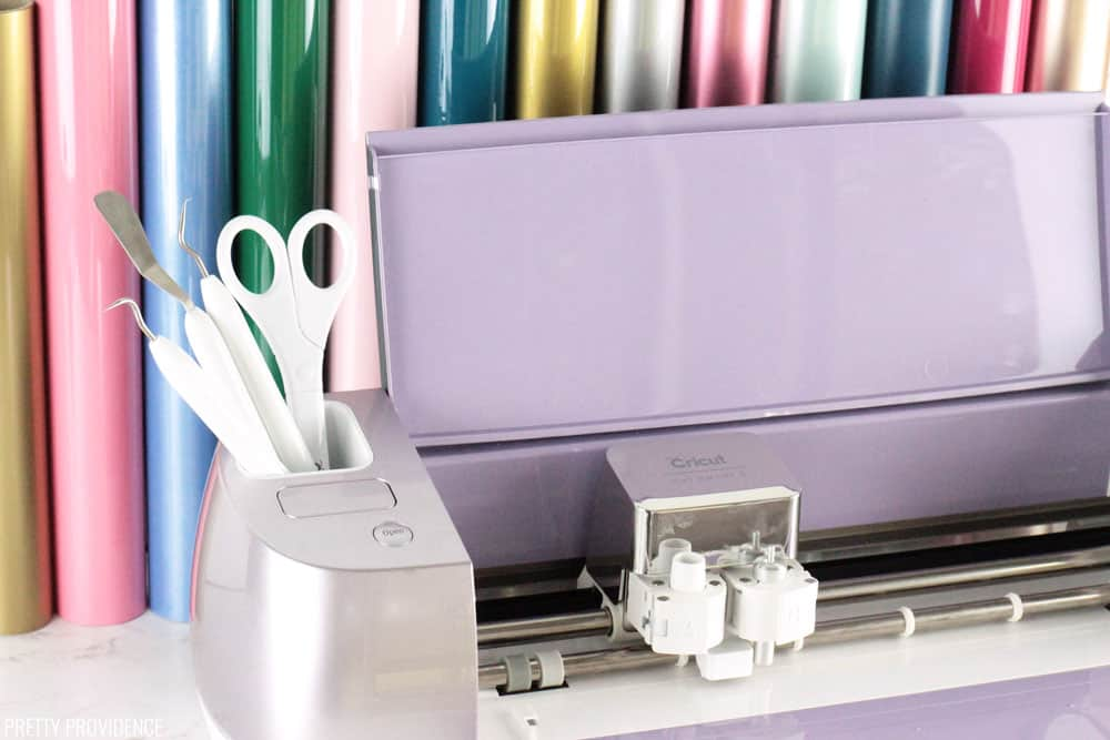 Cricut Explore Air 2 Wisteria (lilac) with cricut tools in and rolls of vinyl behind it.