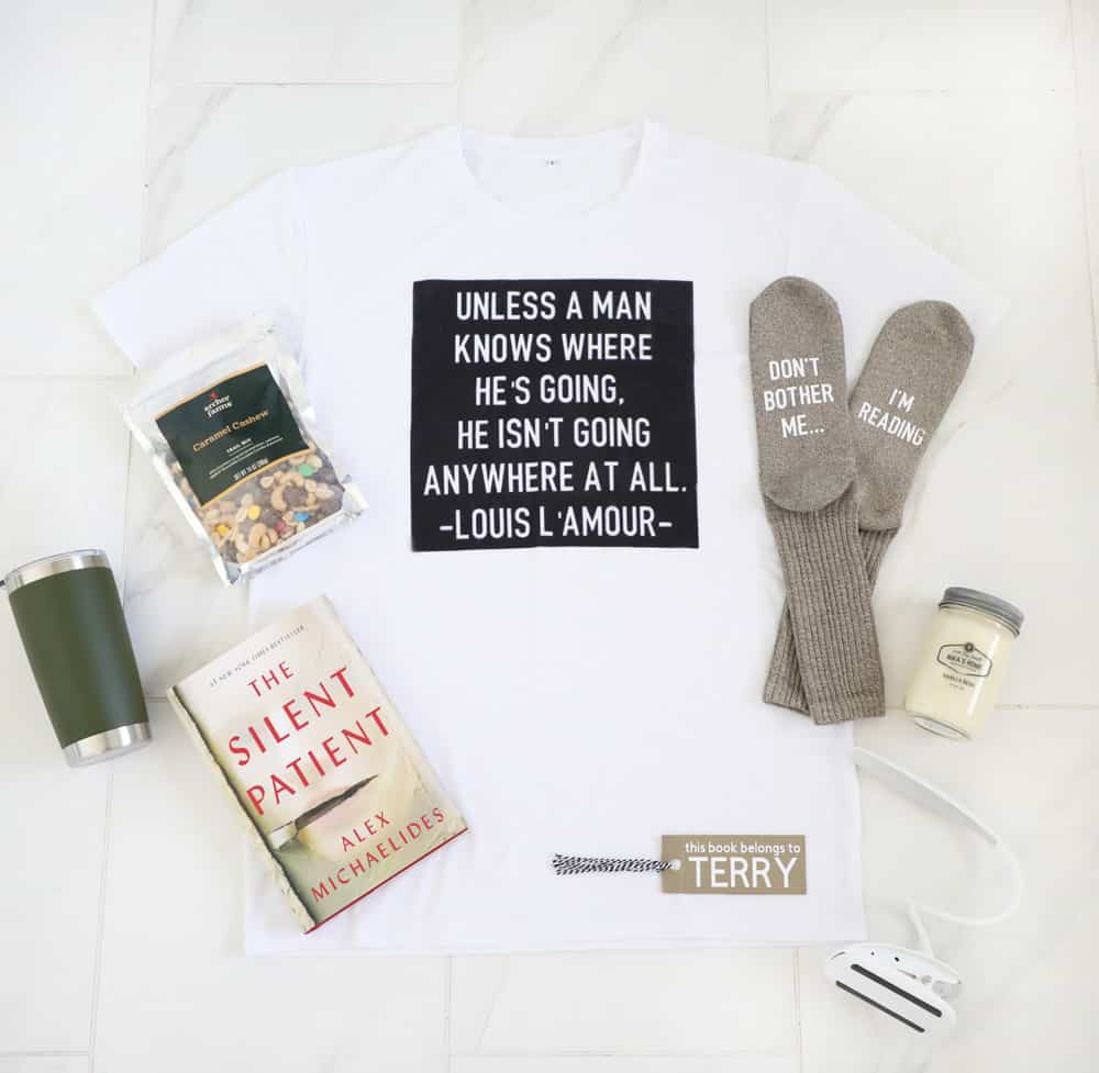 flat lay of a t-shirt, socks, book, reading lamp, bookmark, candle and trail mix