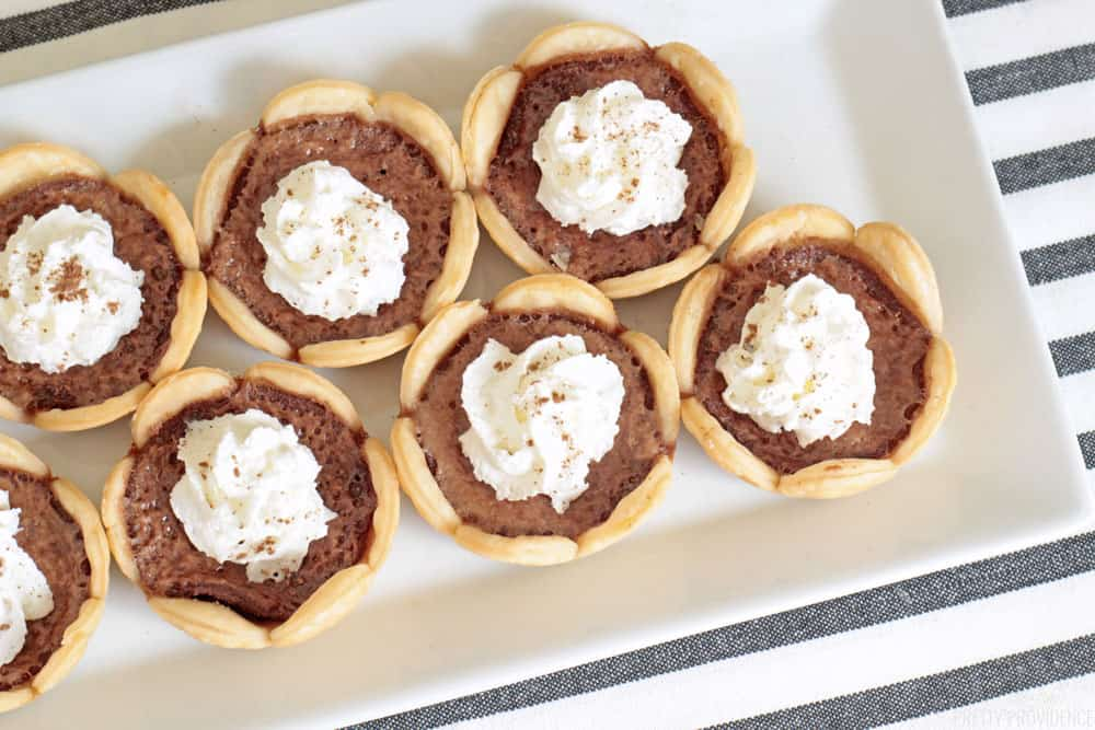 Mini pies with scalloped crust and whipped cream dusted with cocoa powder.