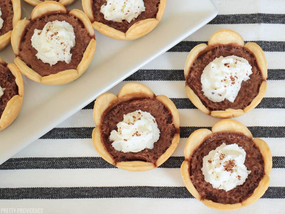 Mini Pies - Chocolate Chess mini pies with scalloped crusts and whipped cream, cocoa powder dusted on top of each.