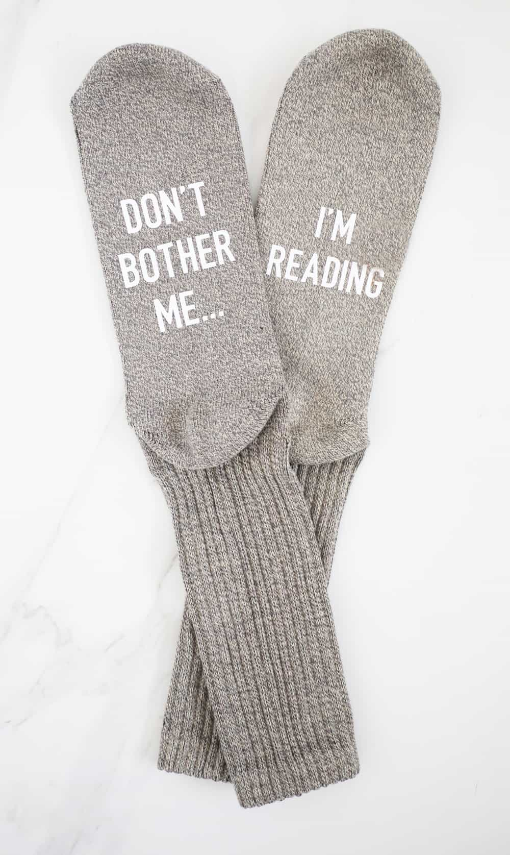 greige socks that say don't bother me i'm reading on a white background