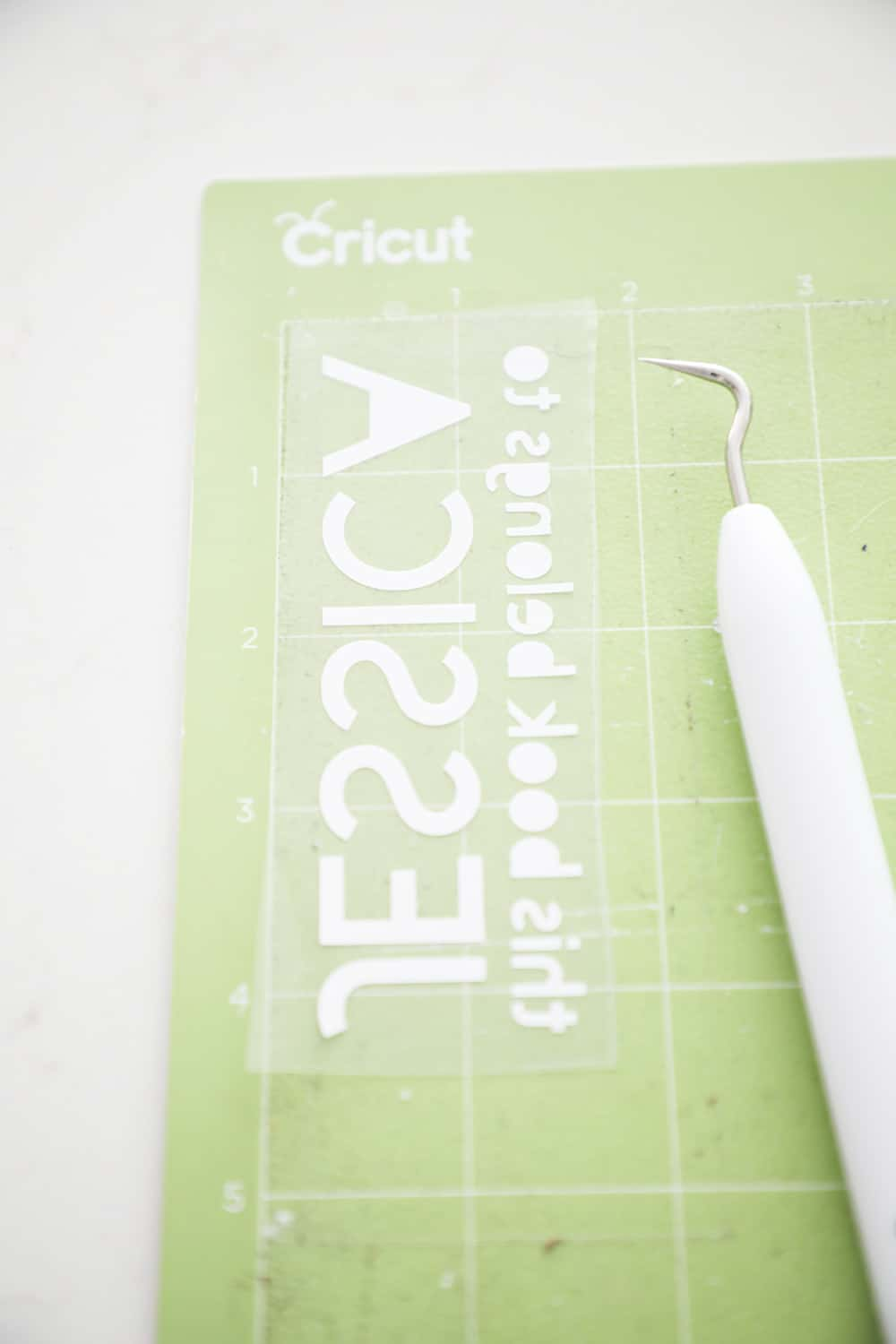 iron on text on a green cricut mat next to a weeding tool