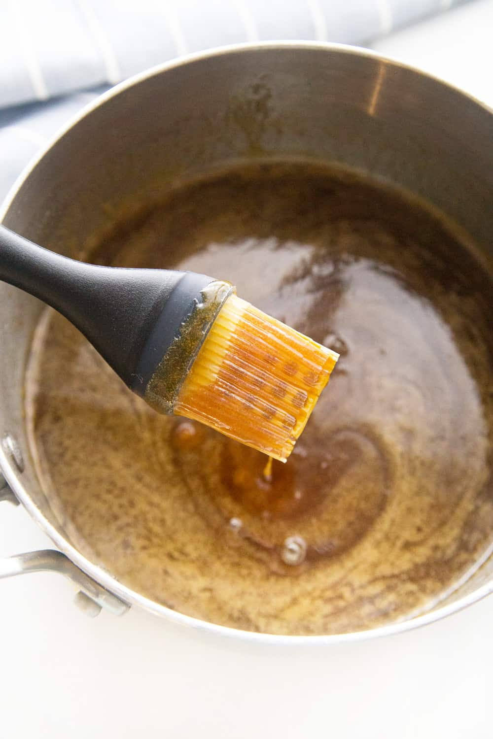 honey glaze dripping off a pastry brush into a metal pan