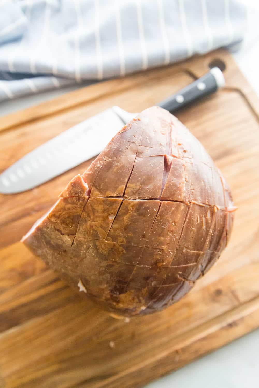 a scored ham sitting on a bamboo cutting board next to a knife