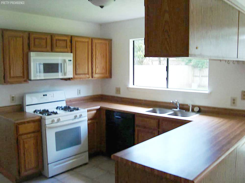 Kitchen Makeover before picture 1980's oak cabinets, mismatched appliances and faux wood laminate counter top.
