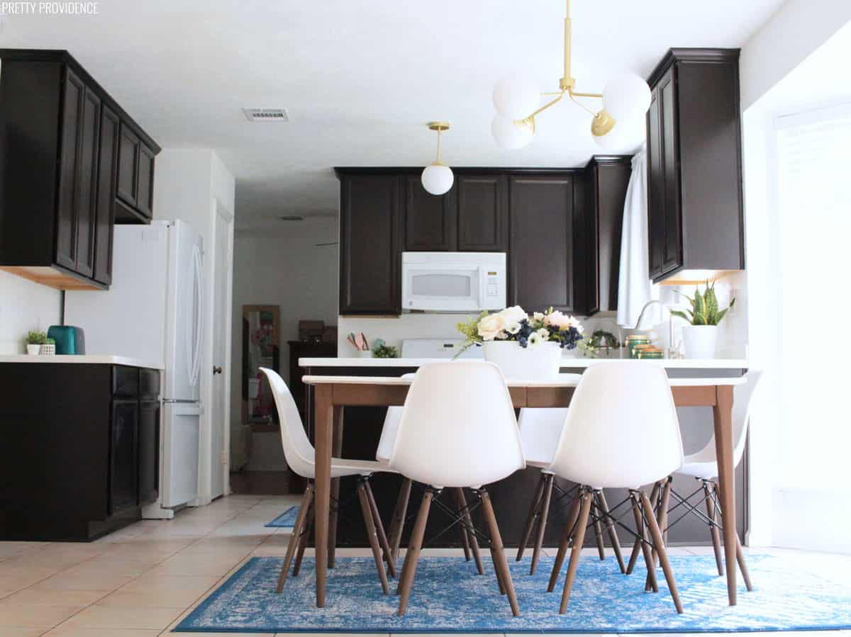 Kitchen makeover with espresso cabinets, white counters, hunter lighting eames style chairs, mid century modern table, blue rugs and accents. Meet Jessica & Sarah - the creative DIY and Decor besties