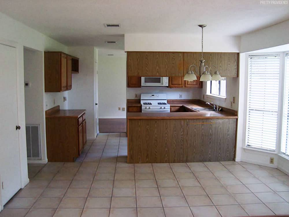 1980's kitchen with brown oak cabinets, tan floor tile and white appliances.