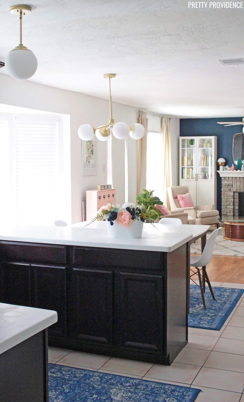 Espresso kitchen cabinets white countertops, gold and white hunter hepburn chandelier, flowers.