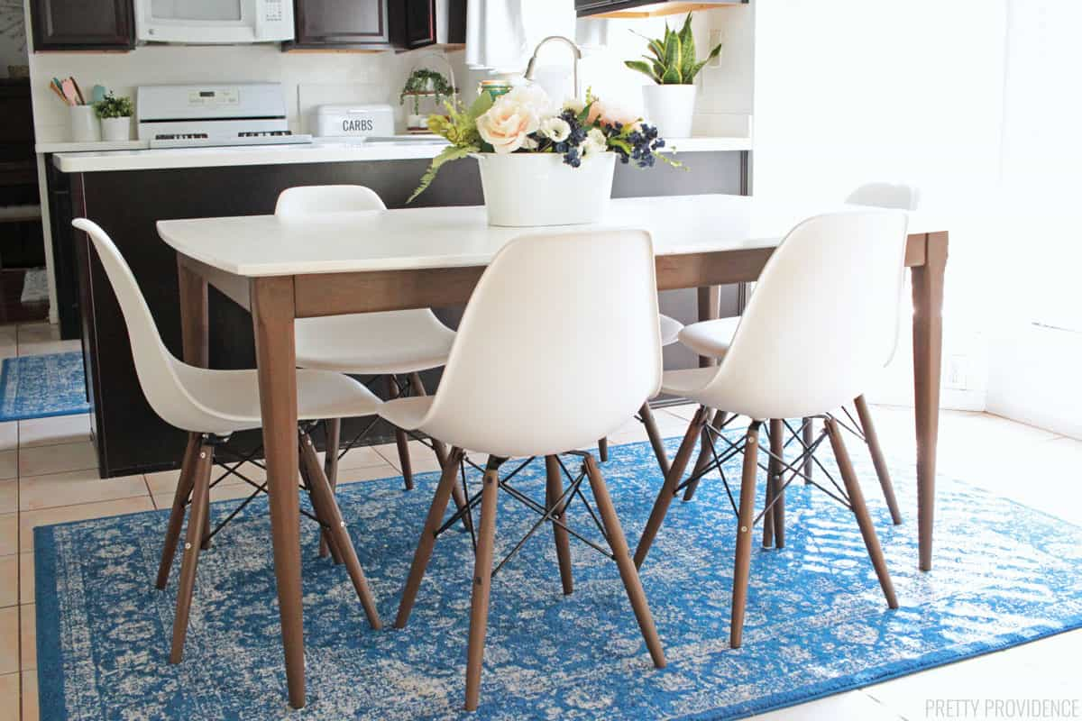 Mid century modern table and eames style chairs in a kitchen on a blue rug.