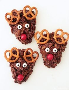 Three reindeer cookies made with cornflakes, marshmallows, pretzels, chocolate and candies.