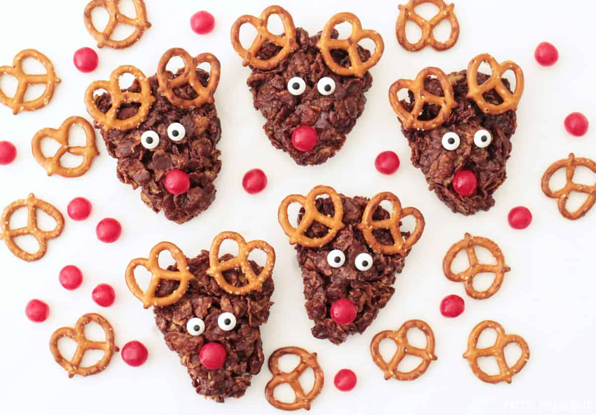 Five No Bake Reindeer Cookies with pretzels for antlers, cherry sours for noses and candy eyeballs.