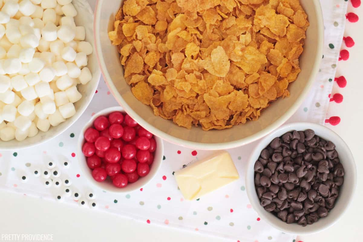 Overhead photo of ingredients: a bowl full of corn flakes, bowl of marshmallows, cherry sours, chocolate chips and a stick of butter.