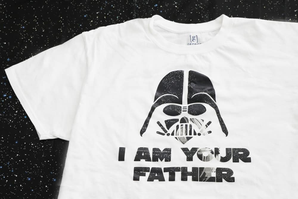 close up of white I am your father shirt against a black background