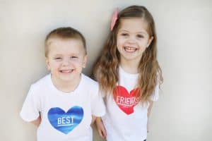 "a boy who's shirt says ""best"" in a blue heart next to a girl who's shirt says ""friends"" in a pink heart"