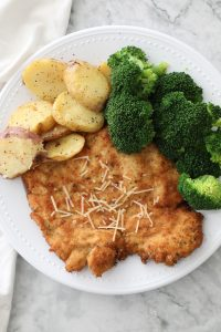 chicken schnitzel on a white plate with broccoli and potatoes