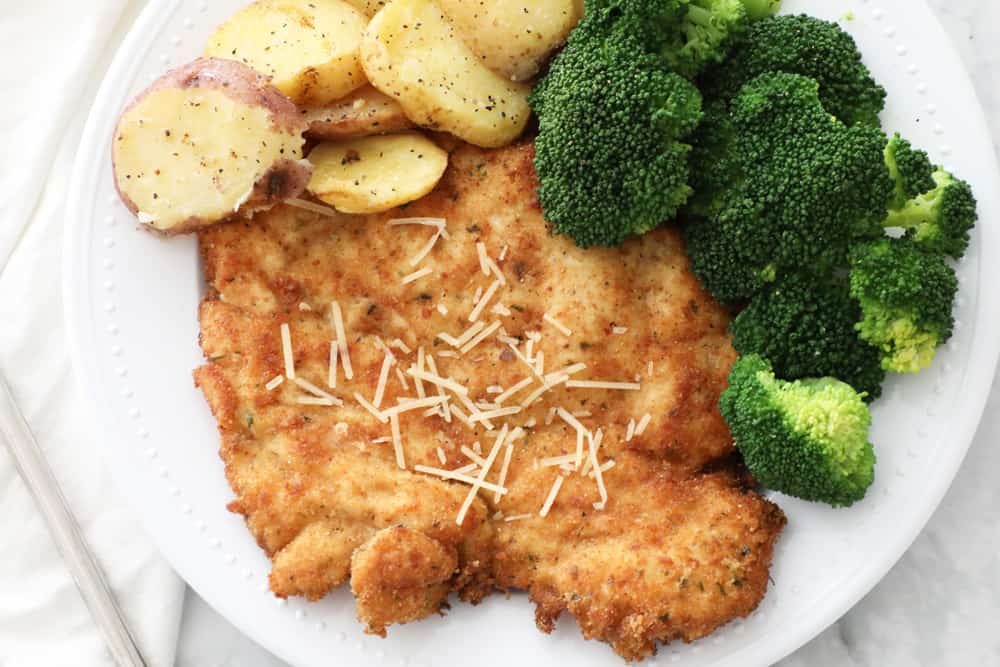 chicken schnitzel next to broccoli and potatoes on a white plate