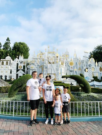 a family at disneyland in front of its a small world wearing matching family star wars shirts