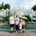 a family at Disneyland in matching Star Wars shirts in front of it's a small world