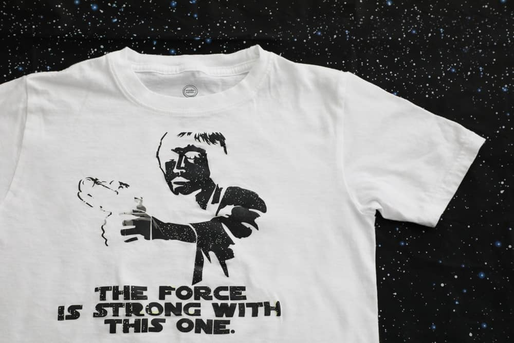 "white shirt with a black Luke Skywalker silhouette that says ""the force is strong with this one"""