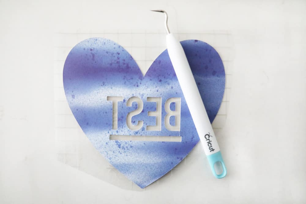"""a blue, weeded, infusible ink heart that says """"best"""" with a weeding tool over it"""