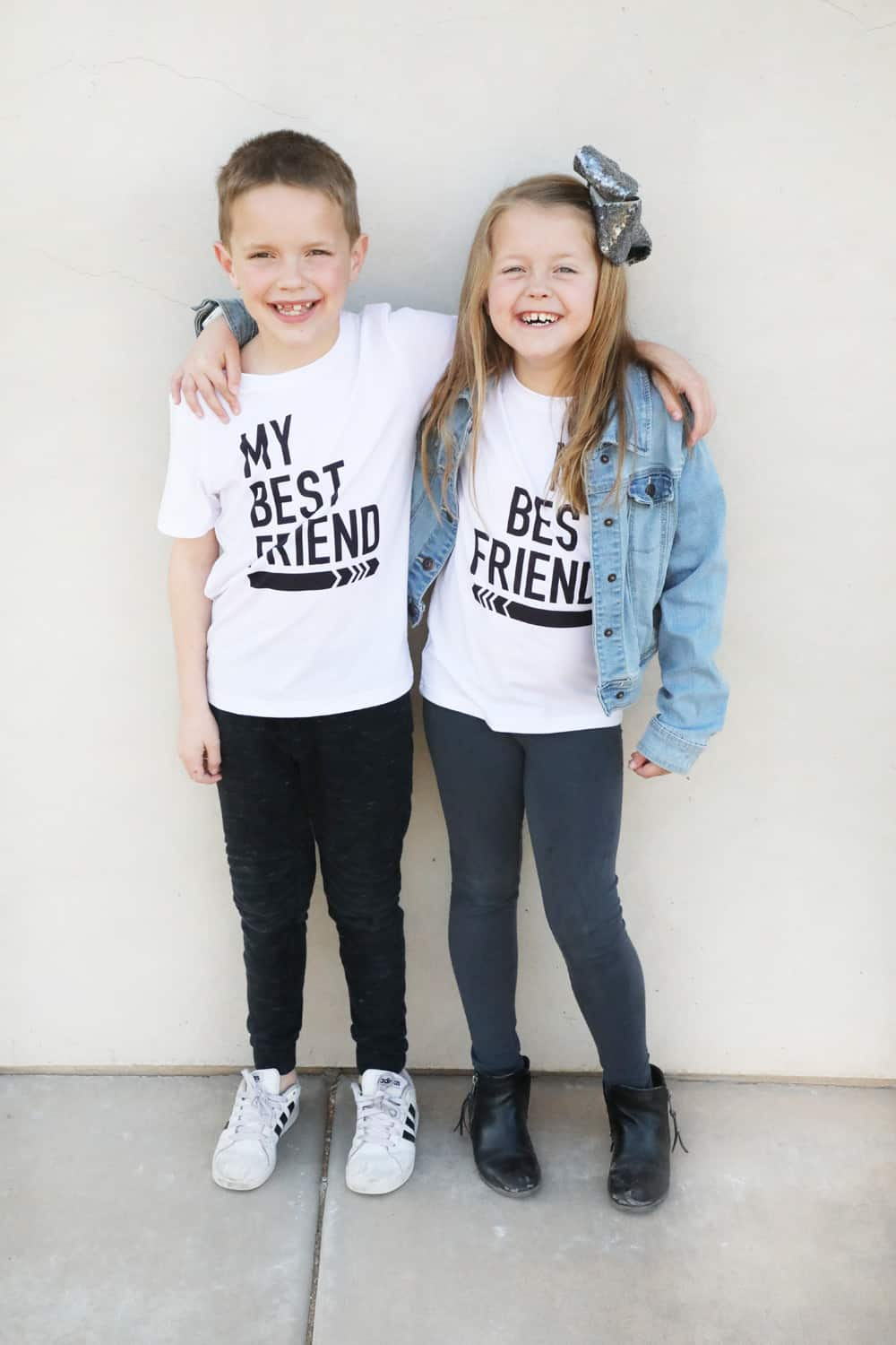 "a boy and a girl in white ""my best friend"" shirts with black writing and arrows pointing toward each other"