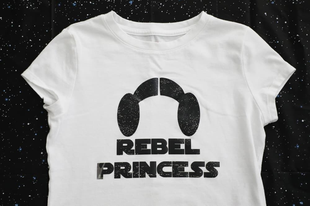 "white t shirt that says ""rebel princess"" and has princess leia buns."