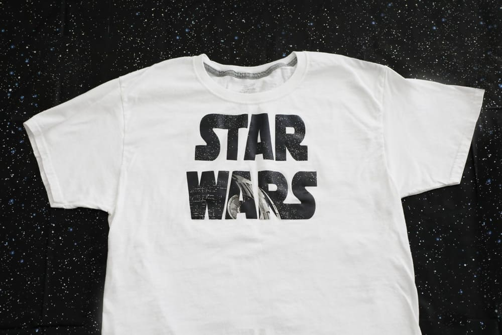 "white shirt with words ""star wars"" in black against a black back ground"