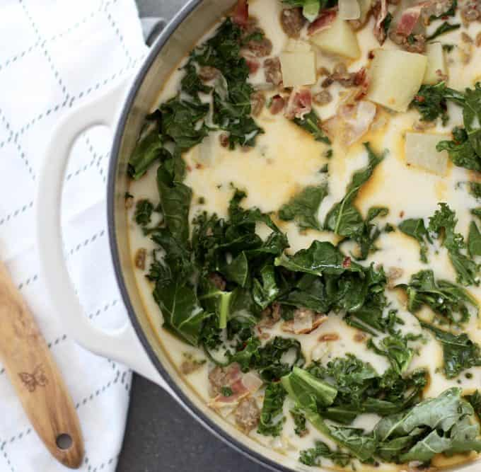 large white pot of Zuppa Toscana soup on a cement counter next to wooden spoon and tea towel