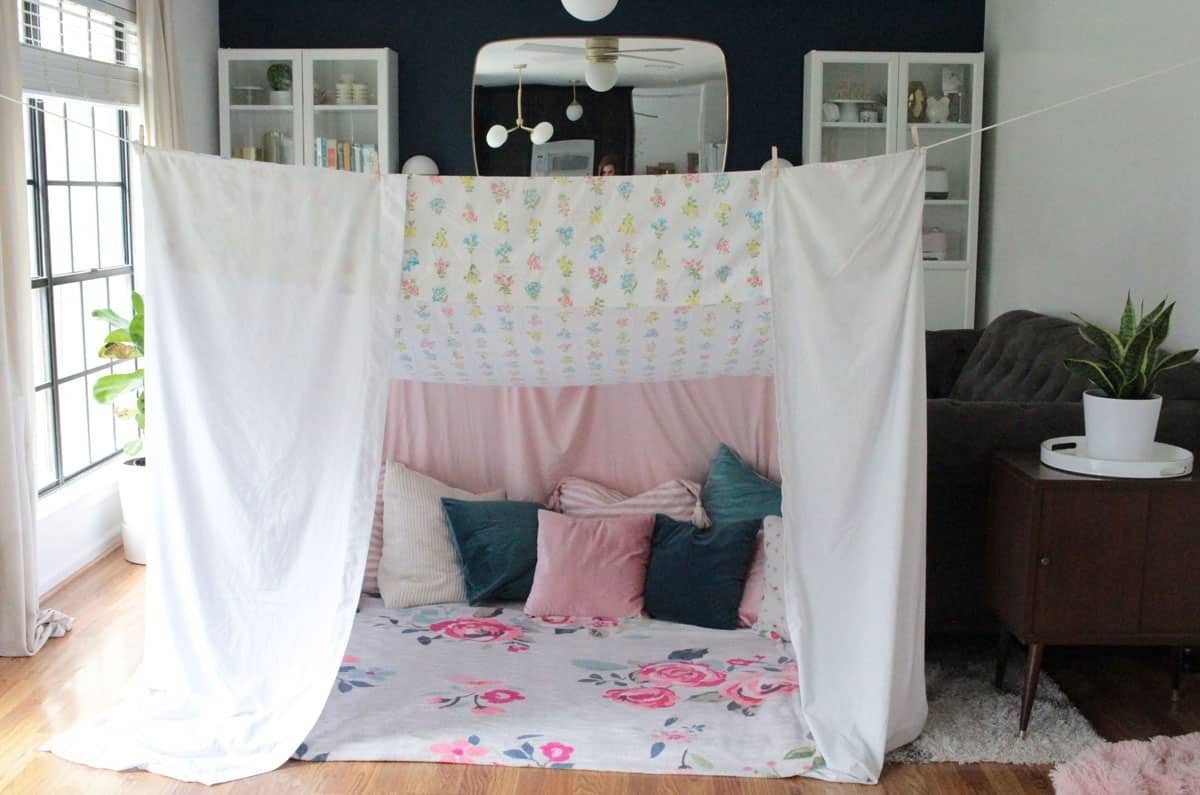 Canopy blanket fort living room tent made from white bed sheets, pillows, blankets and held up by clothes line, clothes pins and chairs.