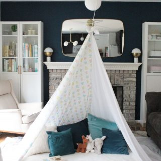 Teepee style blanket fort made with bedsheets and clothesline hung from a light fixture.