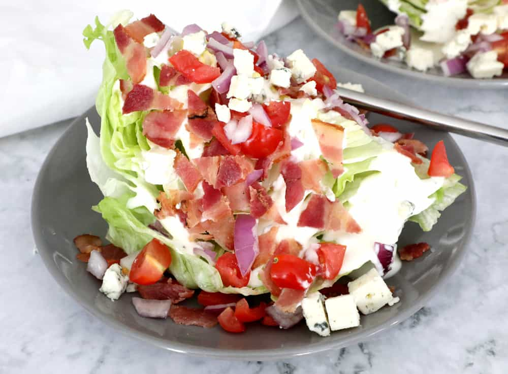 close up of wedge salad with lots of toppings on a small grey plate