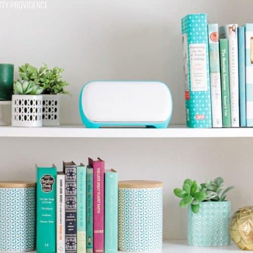 Cricut Joy machine on a bookshelf between books and plants.