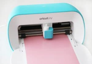 Cricut Joy cutting personalized stickers out of pink vinyl