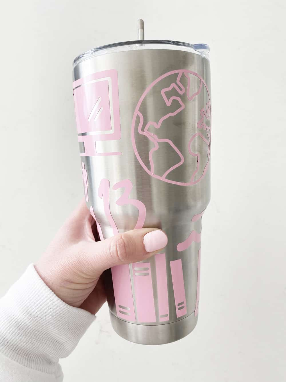 hand holding sticker covered tumbler in front of a white wall