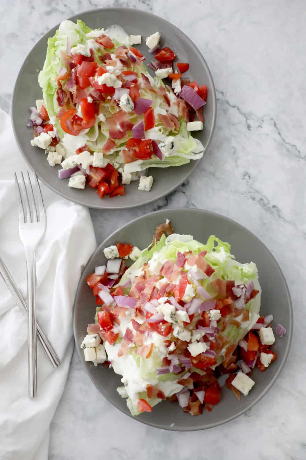 two wedge salads on grey plates next to white cloth napkin and forks