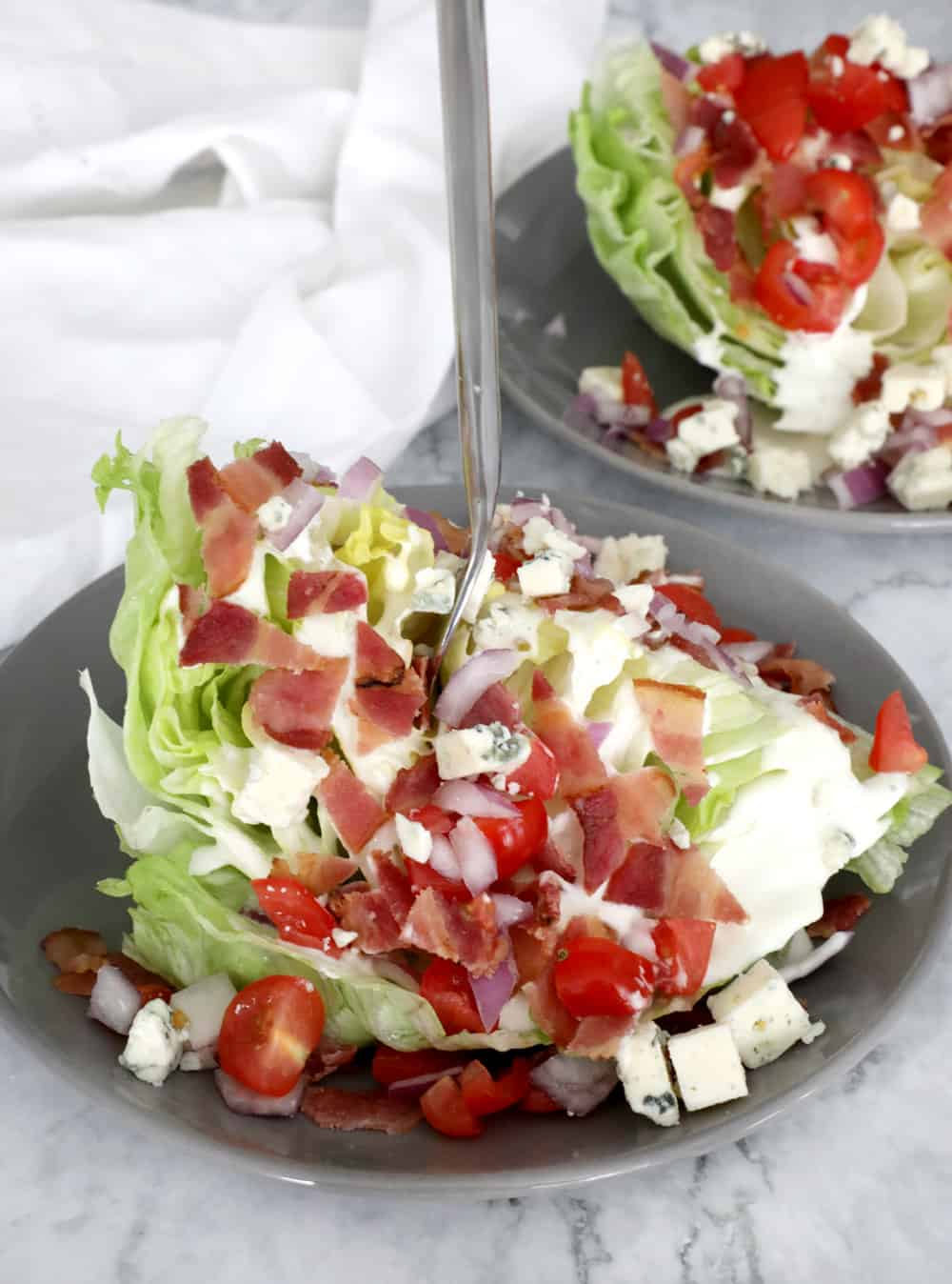 wedge salad with a fork sticking straight out into the air