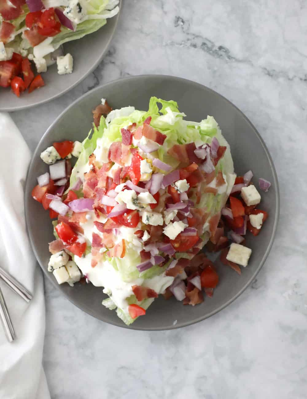 wedge salad on a grey plate on a marble counter with a white napkin on the left