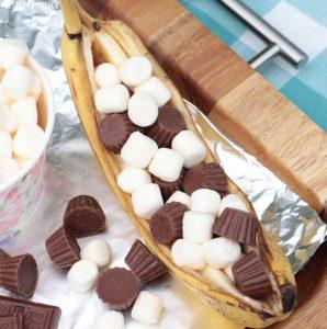 Campfire banana boat dessert - banana stuffed with chocolate and marshmallows on tin foil.