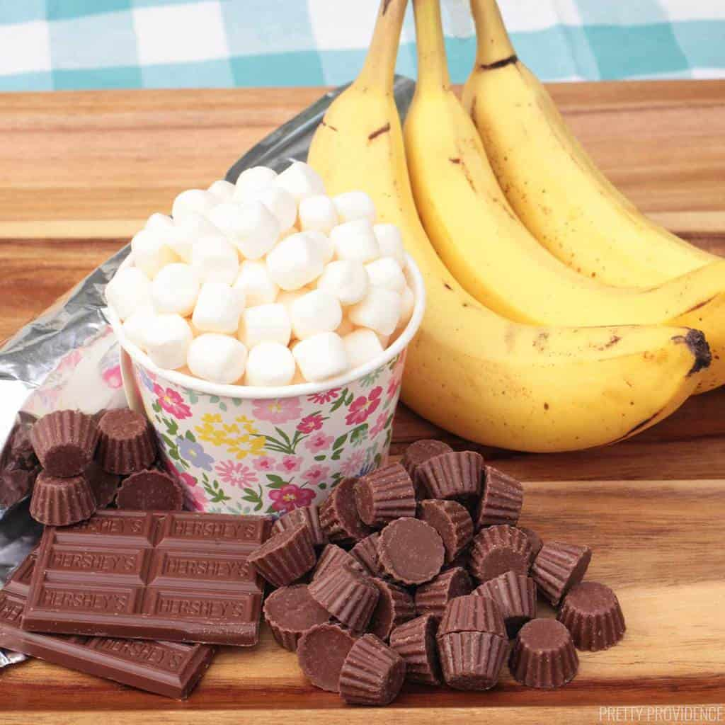 Bananas, mini marshmallows, mini Reeses chocolate and Hershey bars on a wood tray.