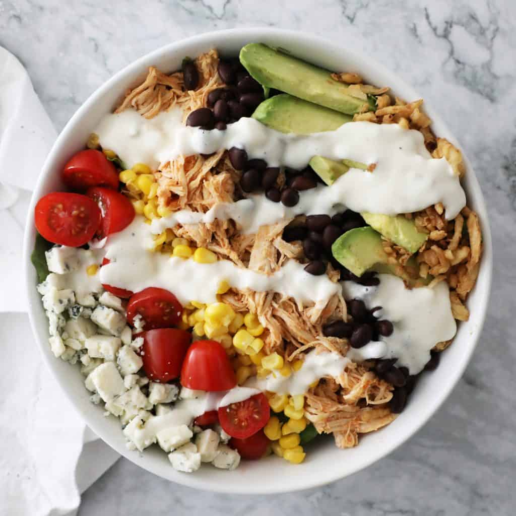 buffalo chicken salad in a white bowl on a granite countertop