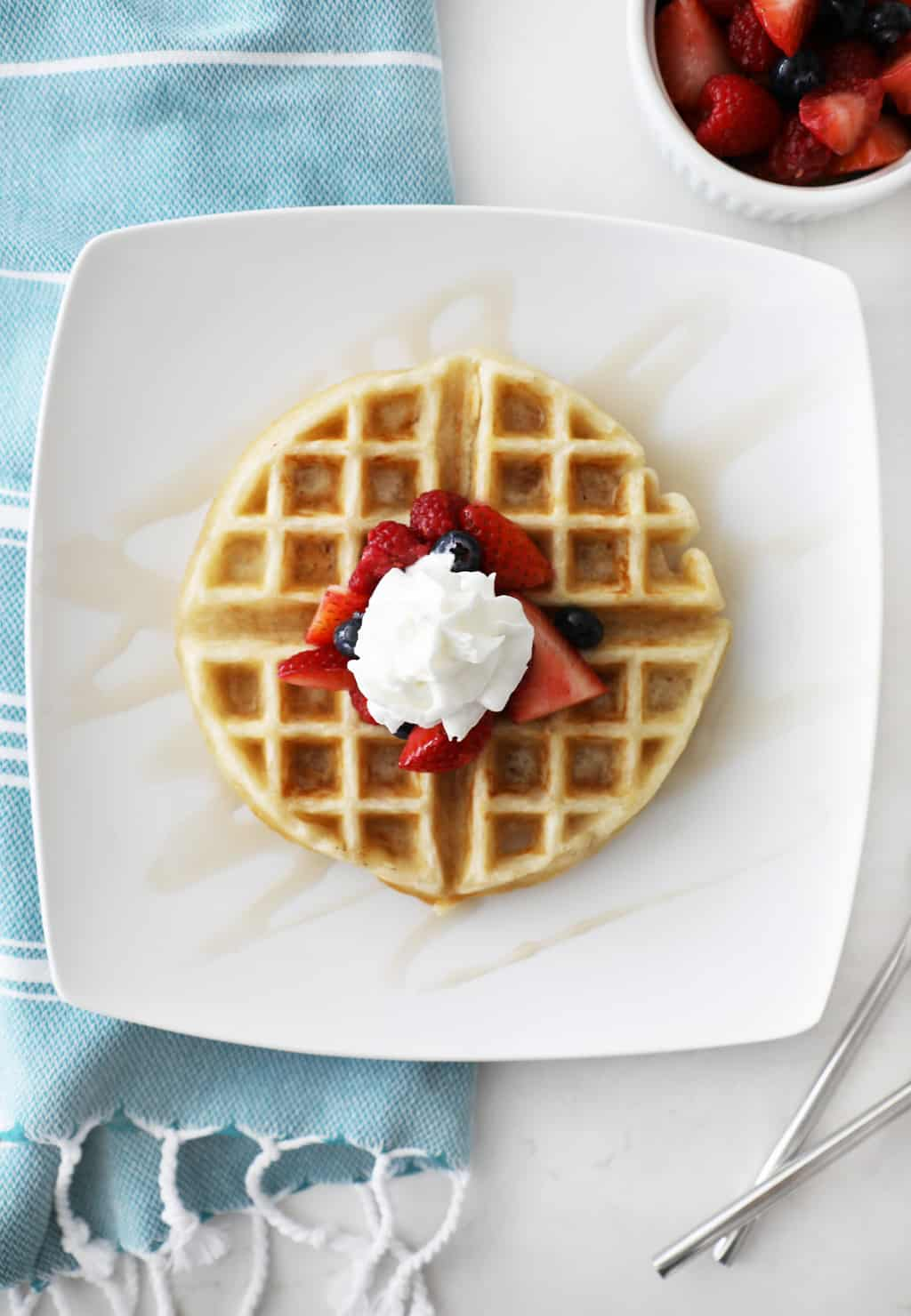 yeast waffle on a white plate with berries and whipped cream