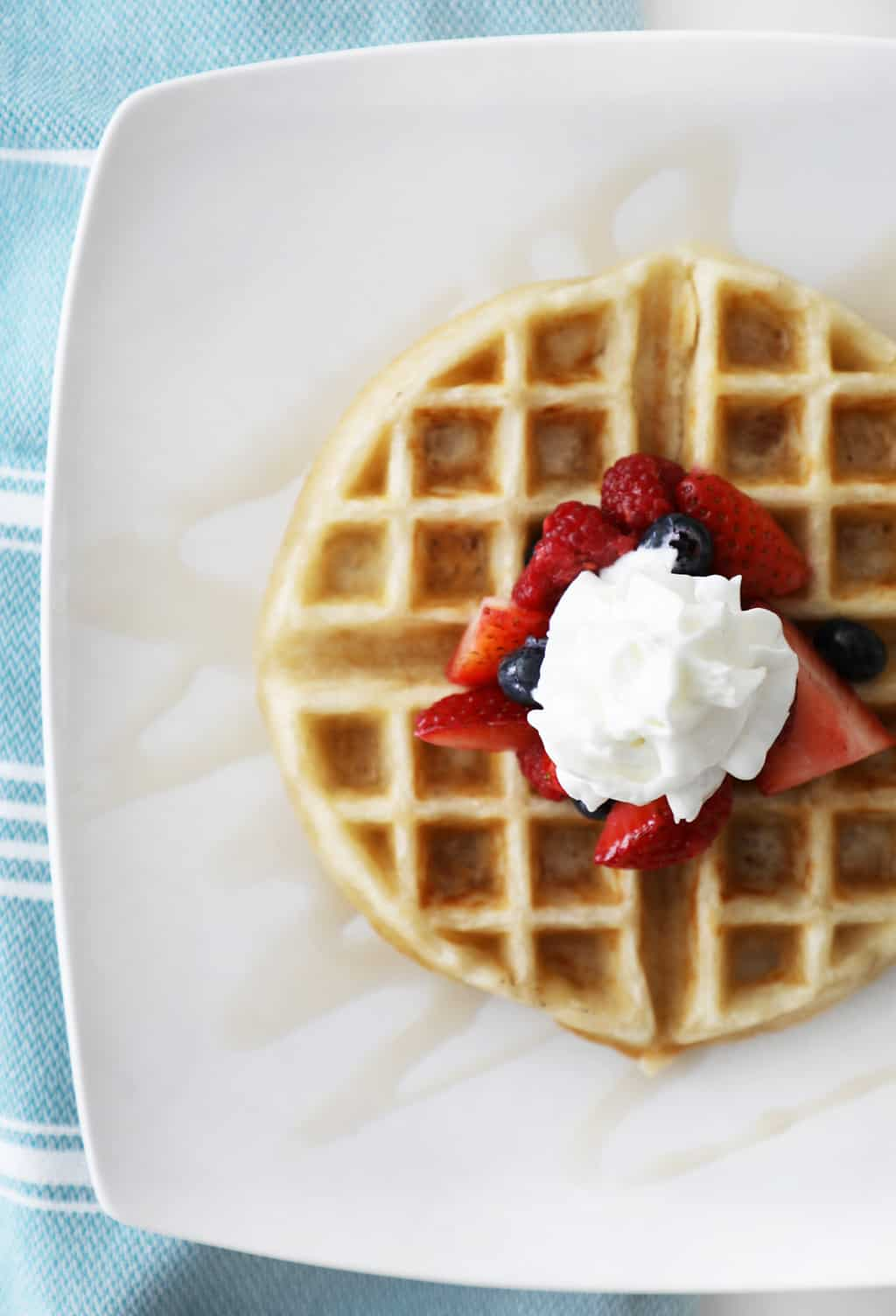 birds eye view of a Belgian waffle with berries and whipped cream