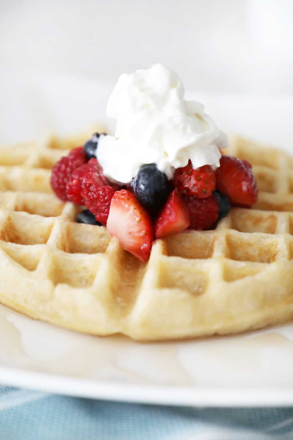 waffle on a white plate topped with berries and whipped cream