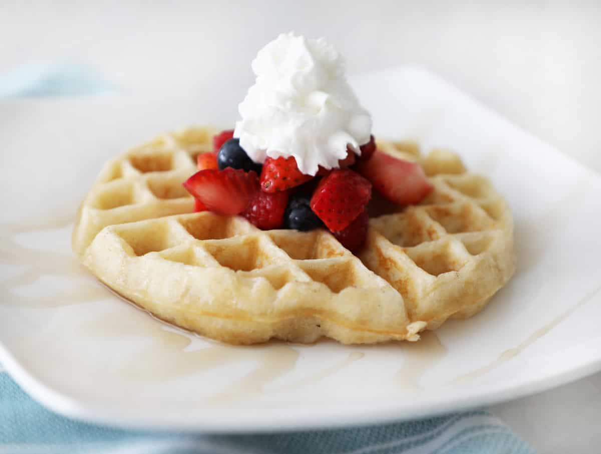 side view of a round waffle on a white square plate topped with fruit and whipped cream