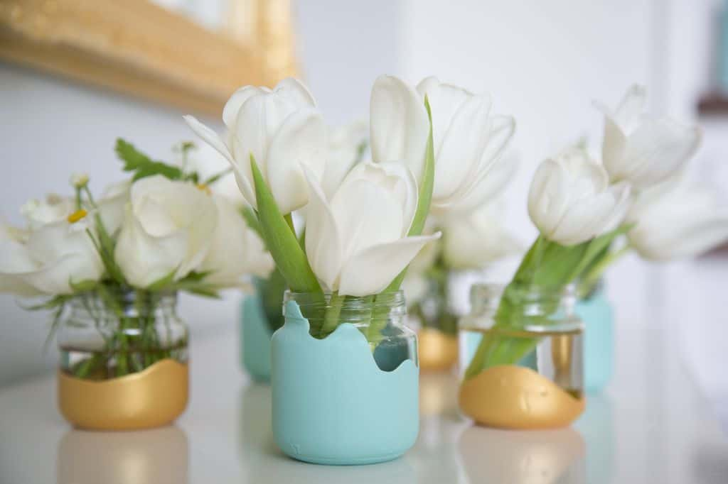 Paint dipped baby food jars with white flowers in them