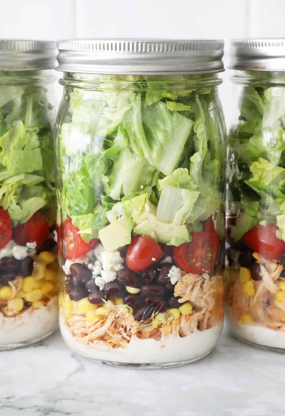 three mason jars filled with salad sitting on a granite counter