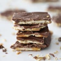 stack of saltine toffee on a white counter with crumbs surrounding it