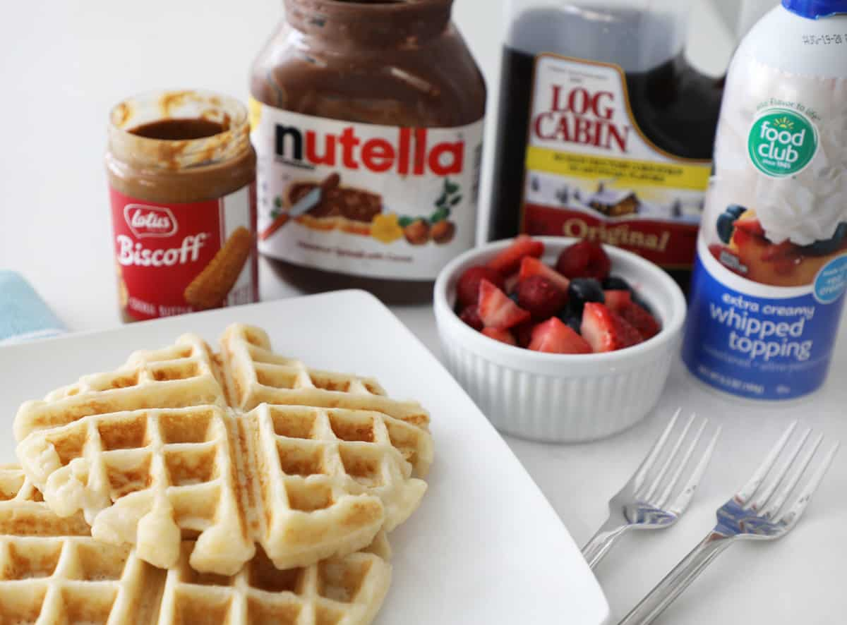 a few waffles on a plate in front of various toppings, cookie butter, nutella, fruit, etc.