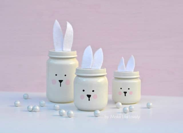 mini easter jars painted white with bunny ears and faces for decoration.