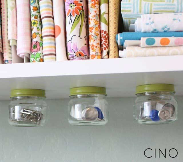 baby food jars screwed onto the underside of a shelf and used as small craft supply storage